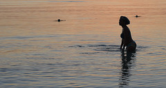 Sunset Swim (Poocher7) Tags: water ocean caribbeansea ripples reflections sunset wading hat buoys bikini portrait people female prettywoman montegobay mobay jamaica caribbean westindies silhouette wadinginthewater
