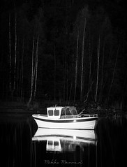Chained in Darkness (Mikko Manner) Tags: nikond7200 nikon80200mmf28af vintageglass vintagelens blackandwhite bw boat sea water reflection reflections sunrise woods trees birch dark darkness shadows shades atmospheric moody