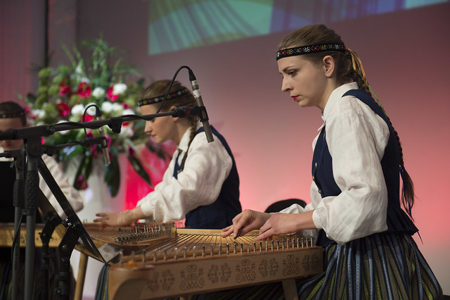 Latvian performers concentrating as they play the Kokle