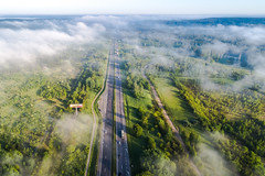 Aerial view of highway covered by early morning fog (spot-on.lt) Tags: shadow spring landscape scrub lithuania tower item hills coniferousforest deciduouswoods clouds plains trees sky drone road sunrise highway forest car morning djiphantom4pro fog sunny europe geometry vilnius p4pro phantom phantom4pro travel above aerial building capital city hill sunshine transportation vegetation vehicle woods