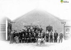 tm_7208 - Stallängens gjuteri 1904 (Tidaholms Museum) Tags: svartvit positiv gjuteribyggnad exteriör fabriksarbetare tidaholm gruppfoto 1904 människor