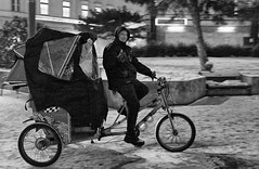 Thumbs Up (tcees) Tags: deákferenctér budapest hungary man cyclist taxi tree snow snowing bench anorak urban x100 fujifilm finepix bw mono monochrome blackandwhite pedicap rickshaw cycle hire night dark thumb fashionstreet streetphotography street bike road