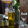 A bottle of olive oil on the table. Two glasses of water. Vase with Flowers. The salt cellar (yannamelissa) Tags: table oil restaurant pepper salt bottle olive cellar green white greece dishware lunch cup athens vinegar ashtray napkins toothpicks food paper shiny glass tourism horizontal eating dish stand capital cafe spice sauce stainless touristic napkin cutlery tablecloth silverware flatware neat tavern decoration design interior cooking