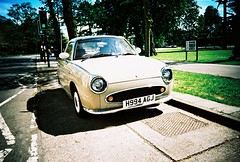 ot500 - nissan figgy (johnnytakespictures) Tags: olympus trip500 compact automatic film analogue lomo lomography xprochrome100 xpro crossprocessed crossprocess 35mm leamingtonspa leamington vintage retro old car vehicle transport figgy nissan figaro street shiny cool japanese pale beige cream brown
