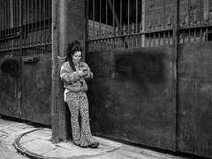 Northern Quarter 232 (Peter.Bartlett) Tags: manchester noiretblanc unitedkingdom people facade olympuspenf woman cigarette urban peterbartlett standing girl streetphotography candid uk m43 microfourthirds mobilephone bw smoking niksilverefex blackandwhite monochrome city england gb