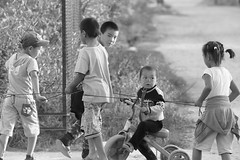 Karakol Kid Play (peterkelly) Tags: bw digital canon 6d asia kyrgyzstan gadventures centralasiaadventurealmatytotashkent karakol street tricycle trike child children boy girl hat string playing