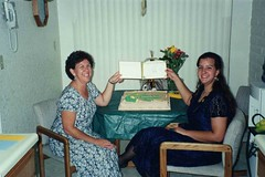 Showing off the Diploma (BarryFackler) Tags: trinafellbaum trinaleefellbaum classof1999 canyondelorohighschool orovalleyaz arizona highschoolgraduation highschool 1999 event occasion milestone familyhistory ceremony diploma bettyfackler bettybowen betty indoor sonoranterraces apartment cake flowers motheranddaughter happy table chairs barryfackler barronfackler smile smiling family people