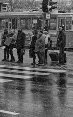 This Snow Is A Pest (tcees) Tags: deákferenctér budapest hungary pest urban x100 fujifilm finepix snow snowing sidewalk pavement streetphotography street road crossing traffic tram people pedestrians man woman luggage hat scarf bw mono monochrome blackandwhite