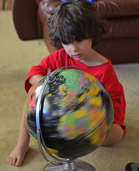 Taking It Out For A Spin (MPnormaleye) Tags: 35mm unposed kids children boy toddler child utata globe world sitting