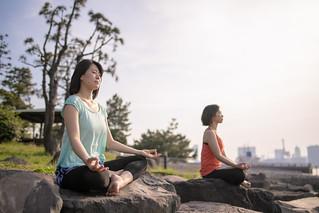 Two women practicing yoga on rock