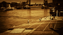 Walking on concrete (STEHOUWER AND RECIO) Tags: people girl walking concrete water bridge view movie film sepia moment shore lunchbreak summer hot rotterdam netherlands dutch holland man woman women lines perspective monochrome candid pov vintage classic retro