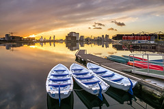 Sunset over Royal Victoria Docks Jetty (adrians_art) Tags: water royalvictoriadocks isleofdogs uk england london docklands reflections silhouettes shadows sky clouds urban people sunburst boats jetty pier orange yellow red gold blue