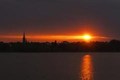 Ein Licht am Horizont (Lilongwe2007) Tags: hamburg deutschland sonnenuntergang kirchturm silhouetten ausenalster alster wasser spiegelung glück wolken farben st johannis