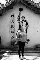 When the chairman is watching you... (Go-tea 郭天) Tags: qingdaoshi shandongsheng chine cn qingdao huangdao cangmashan moutain village old traditional tradition ancient building history historical historic wall painting mao communist revolution party young lady sun sunny shadow hot warm glasses house leader canon eos 100d 50mm prime street urban city outside outdoor people candid bw bnw black white blackwhite blackandwhite monochrome naturallight natural light asia asian china chinese shandong portrait