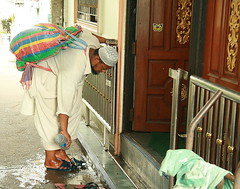 at the door of the mosque (the foreign photographer - ฝรั่งถ่) Tags: man washing feet moslem muslim shoes door stainless steel gate khlong thanon portraits bangkhen bangkok thailand canon ramadan first day