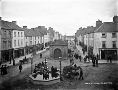 A hive of activity - Main Street, Roscrea, Co. Tipperary (National Library of Ireland on The Commons) Tags: robertfrench williamlawrence lawrencecollection lawrencephotographicstudio thelawrencephotographcollection glassnegative nationallibraryofireland roscrea countytipperary fountain donkeys carts traffic pedestrians markethouse lamps dog postoffice
