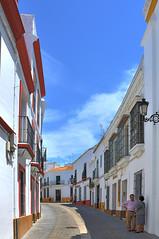 Carmona ( Province of seville )  : Post Street (Pantchoa) Tags: carmona seville andalousie espagne rue photoderue ciel bleu perspective paysage ville maisons immeubles façades couple personnes deux personne urbain nuage