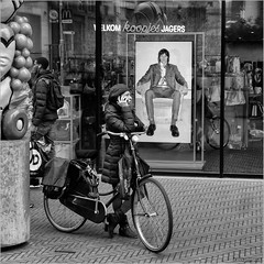 The chairman is watching you (John Riper) Tags: johnriper street photography straatfotografie square vierkant bw black white zwartwit mono monochrome netherlands candid john riper sgravenhage denhaag thehague fuji fujifilm xt2 18135 poster man sitting chair bicycle bike woman lady cap phone ringing reflections bags