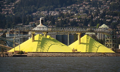 Sunlight & shadows over the North Shore sulphur piles (Reva G) Tags: yellow sulfur sulphur piles mountain industrial refinery factory northshore northvancouver industry shadow ocean burrardinlet water waterfront