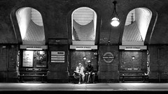 The couple (images@twiston) Tags: bakerstreet london underground baker street metro tube urban streetphotography candid marylebone train station hammersmithcityline circleline platform5 skylights tiled dark victorian imagestwiston bakerst people couple commuter architecture brickwork waiting engrossed mobile smartphone classiclondon lowlight bw mono blackandwhite noirblanc monochrome blacknwhite eastbound