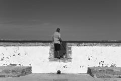 El pescador - The fisherman (Explored) (ricardocarmonafdez) Tags: cádiz streetphotography ciudad city cielo sky sunlight people mar sea fishing fisherman symmetry monocromo monochrome blackandwhite bw bn 60d 1785isusm canon