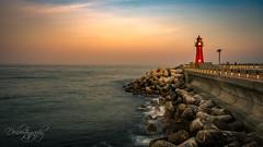 Red Lighthouse at Sunset (Deibertography) Tags: daepoport southkorea boardwalk breakers clouds coast landscape lighthouse nature ocean red rocks sea shore sky sunset tetrapods tide waves pier