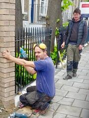 Fitting the railings. (gerrypopplestone) Tags: railings peckham london workers pavement