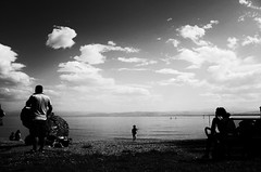A day at the lake (stefankamert) Tags: stefankamert lakeconstance bodensee lake people noir blackandwhite blackwhite grain highcontrast noiretblanc water ricoh gr grii clouds sky beach landscape