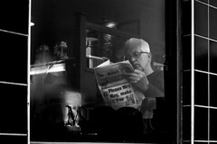 I read the news today, oh boy.....  About a lucky man who made the grade. And though the news was rather sad, Well, I just had to laugh...... I saw the photograph! (markfly1) Tags: bw man cafe window reading newspaper black white mono glazed tiles news gazette post reflections candid street nikon d750 england uk portsmouth focus lens
