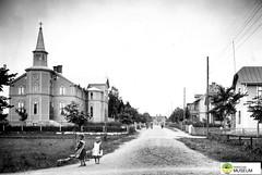 tm_7434 - Karlavägen, Tidaholm (Tidaholms Museum) Tags: svartvit positiv tidaholm exteriör grusväg kyrka bostadshus