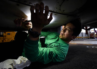 A Sailor removes a panel from the bottom of an MH-60S Sea Hawk helicopter.
