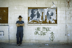 live free or die (Super G) Tags: niland california unitedstates us saltonsea corvinaestates abandoned building block poster graffiti selfportrait hat microphone wall standing
