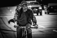 Rough Rider on Bank Street (Dan Dewan) Tags: 2018 canonef70200mmf14lisusm dandewan bicycle street people person blackwhite canon hat man ottawa spring wednesday ontario canada bw may portrait cyclist