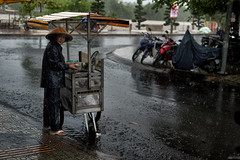 Selling in the rain. Monsoon season in Vietnam. Near the Mekong delta, just outside the market, this lady sell some soup. (rvjak) Tags: bentre vietnam southeast asia asie sudest d750 nikon woman femme pluie rain mekong delta river street rue marché market hat chapeau fx