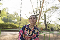 Young  Asian woman in kimono sitting on swing in public park (Apricot Cafe) Tags: img89125 asia asianandindianethnicities japan japaneseculture kimono malaysianethnicity positiveemotion tamronsp35mmf18divcusdmodelf012 tokyojapan backlit charming copyspace cultures day hairtoss happiness inokashirapark lifestyles nature oneperson oneyoungmanonly oneyoungwomanonly outdoors people publicpark satisfaction sitting smiling springtime sunlight swing toothysmile tourism tradition traveldestinations waistup wasitup wind women youngadult