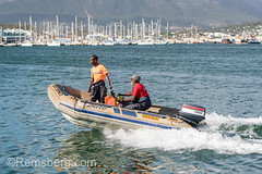 Two men ride a dingy on the water on Hout Bay in Cape Town, South Africa (Remsberg Photos) Tags: africa southafrica capetown coastal seaside westerncapeprovince ocean boat watervessel transportation nauticalvessel onlymen africanmale dingy houtbay westerncape