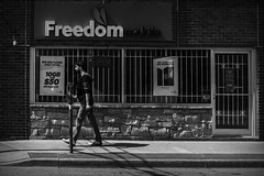 Freedom. Windsor, ON. (Paul Thibodeau) Tags: photooftheday windsor nikond500 35mm streetphotography sign blackandwhite monochrome man walking freedom bars juxtaposition