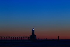 The View of the Chicago Skyline from Michigan City, Indiana (Symbiosis) Tags: lighthouse lakemichigan michigancityindiana chicagoskyline chicago bluehour blue bluelight