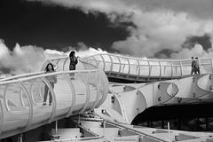 Pasarela en las nubes - Footbridge in the clouds (ricardocarmonafdez) Tags: sevilla metropol setas arquitectura architecture structure cielo sky nubes clouds people streetphotography urbanscape lineas lines curvas curves light shadows sunlight monocromo monochrome blackandwhite bw bn 60d 1785isusm canon geometría geometry ciudad city pasarela footbridge walkway