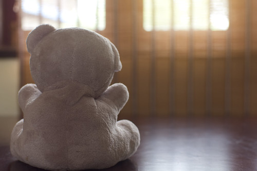 Alone teddy bear sitting on wood table, Sad concept
