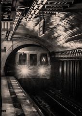 """A"" Train Arriving In Subway Station Manhattan (nrhodesphotos(the_eye_of_the_moment)) Tags: dsc012133001084 ""theeyeofthemoment21gmailcom"" ""wwwflickrcomphotostheeyeofthemoment"" subway mta train trainstation rails metal reflections shadows atrain manhattan nyc underground columns headlights blackandwhite tunnel"
