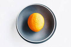 Top view of a single orange in a grey plate . (wuestenigel) Tags: natural color different leaf apple background holiday diet vegetarian ripe fresh white citrus gray gift vitamin fruit delicious orange still juicy plate food red mandarin lemon summer colorful healthy beautiful bright tangerines sweet freshness closeup green fruits yellow care organic