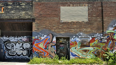 Old factory wall with laneway art - Little Italy, Toronto. (edk7) Tags: nikond300 edk7 2013 canada ontario toronto littleitaly architecture building oldstructure brick graffiti mural laneway wallart factory abandoned industrial city urban weed ibeam