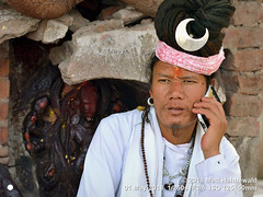 2014-11a Sadhus from Nepal 2018 (02) (Matt Hahnewald) Tags: matthahnewaldphotography facingtheworld character head face forehead tilaka thirdeye eyes expression chinbeard hair hairstyle dreadlocks dreadbun cellphone bodylanguage hand silver crescent candid concept travel culture tradition lifestyle technology communication religion anthropology exotic spiritual religious cultural holy hinduism sadhu guru kathmandu nepal asia asian oneperson male adult young man phone photo temple nikond3100 primelens 50mm horizontal street portrait halflength closeup seveneighthsview white outdoor color authentic serious phoning calling phonecall priest nepali nikkorafs50mmf18g rolledup clarity 4x3ratio 1200x900pixels resized