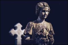 The girl in the graveyard (G. Postlethwaite esq.) Tags: belper dof derbyshire beyondbokeh bokeh boneyard cemetery cross depthoffield girl grave graveyard photoborder selectivefocus statue