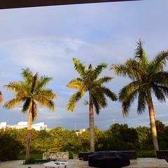 A Rainbow (soniaadammurray - On & Off) Tags: digitalphotography rainbow sky clouds trees architecture garden grass creek stadiumlights pooldeck furniture plants shadows reflections nature artchallenge