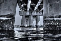 Under the bridge (Maya K. Photography) Tags: bridge piers water ocean bw bwphoto monochrome construction reflection america us usa newyork ny blackandwhite blackandwhitephotography blackandwhitephoto shadows lights daylight summer nikon nikond5000 nikkor flickr underthebridge mayak mayakphotography