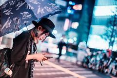 Kabukicho Crossing (Jon Siegel) Tags: nikon d810 50mm 12 bokeh woman raining rain hat fashion umbrella night evening japanese japan tokyo shinjuku kabukicho crossing street people candid glow urban city