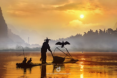 Silhouette of the Cormorant Fisherman II (fesign) Tags: bambooraft bird boat chinaeastasia chineseculture colourimage contrast cormorant fisherman fishing fulllength guilin horizontal karstformation mountain onemanonly oneperson oneseniorman orange outdoors people photography reflection river riverli rurallife senioradult silhouette standing sunlight sunrisedawn threeanimals traditionalclothing twilight water woodmaterial xingping yangshuo