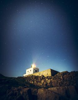 Bamburgh Lighthouse under the stars .